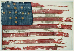 "The ""Hulbert Flag'"" which may have flown over Ft. Ticonderoga during the Jersey Grey's encampment there. This particular flag was likely the first model for the American ""Stars and Stripes."""